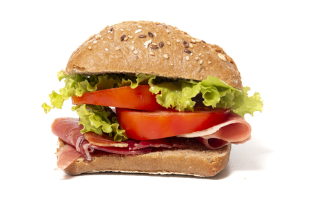 sandwich with ham, tomato and lettuce over a white background.