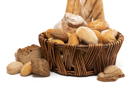 Fresh Assortment of several baked bread varieties inside a wicker basket.