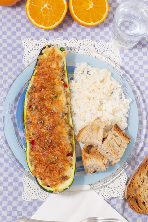 meat and vegetables zucchini halves with rice and bread.
