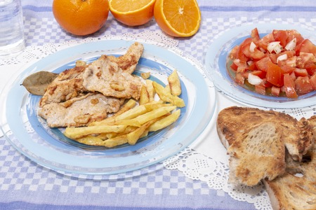 Traditional portuguese meal of Turkey steak with french fries and tomato salad.