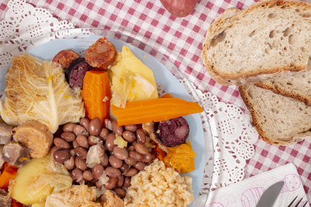 Traditional cozido portuguese boiled stew with beef, bacon, vegetables, beans and smoked sausages.