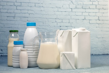Mix of milk bottles and package isolated on a blue brick background.