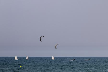 Kitesurf and yacht sailing faraway on the sea. Stock Photo
