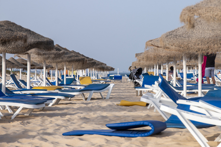 Beach umbrellas with chair recliners on Fuseta in the Algarve region, Portugal. 版權商用圖片
