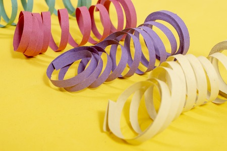 Mixed colorful streamers on a yellow background.