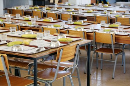 Interior view of an empty school canteen with tables and chairs.