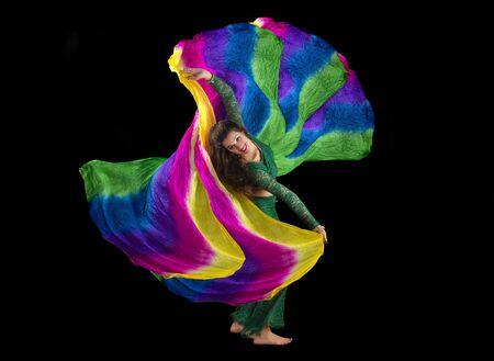 Bailarina de danza del vientre joven exótica aislada en un fondo negro.