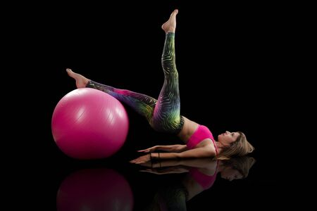 fitness girl exercise with ball on a black background.