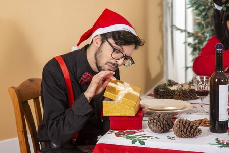 man holding two gifts with christmas santa hat. Stock Photo