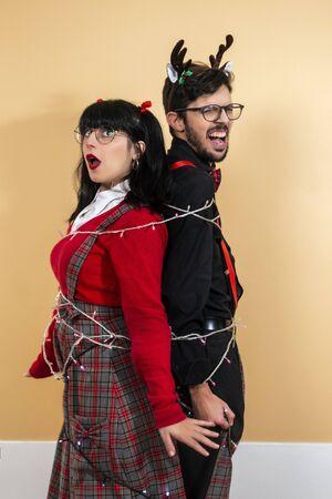 man and woman tangled using a christmas lights cord.