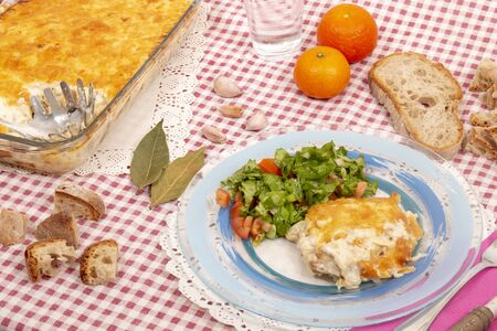 Cod fish with cream, a traditional portuguese dish, with potatoes, onions, olive oil and covered with parmesan cheese, baked on the oven.