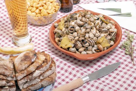 Traditional Portuguese dish of cooked snails and toasted bread and beer. Reklamní fotografie