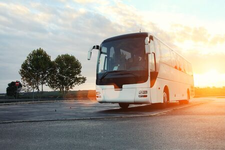 Passenger Bus parked on the road at sunrise.