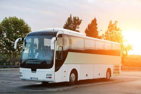 Autobus pasażerski zaparkowany na drodze o wschodzie słońca.