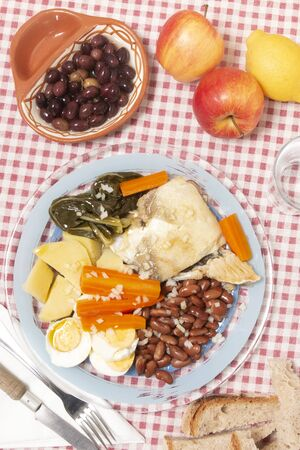 Close view of traditional portuguese dish of codfish with beans and vegetables.