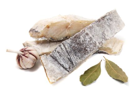 Close up view of pieces of portuguese salted codfish isolated with bay laurel.