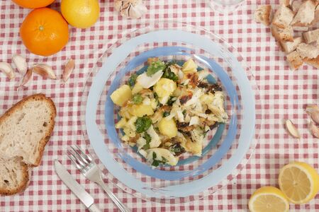 Close view of traditional portuguese dish of Grilled Codfish with potatoes and olive oil.