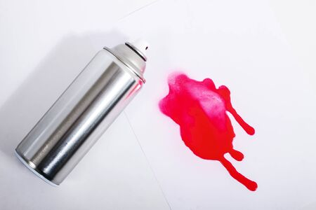 Close up view of a spray can with red paint on a white background. Stockfoto