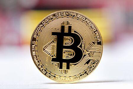 Shiny golden bitcoin commemorative coin closeup.