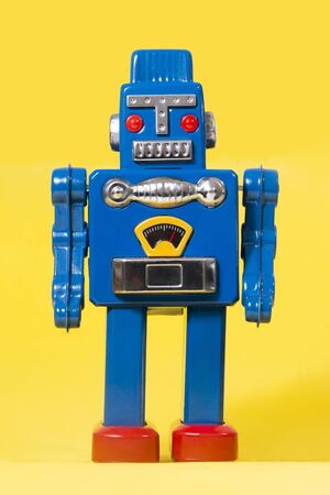 Vintage tin robot toy isolated on a yellow background.