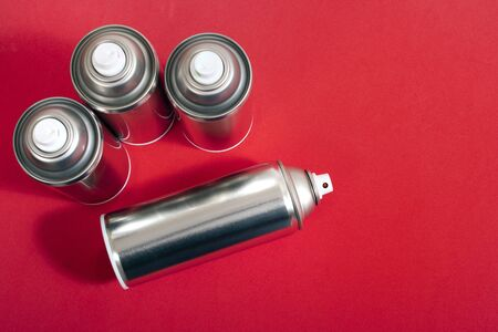 Close up view of silver spray cans on a red background.