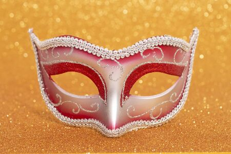 View of a carnival venetian mask on a golden background. Stock Photo