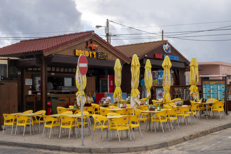 FARO, PORTUGAL: 21th OCTOBER, 2018 - Typical wooden beach bars with yellow plastic chairs that sell snacks, icecream, summer drinks and food.