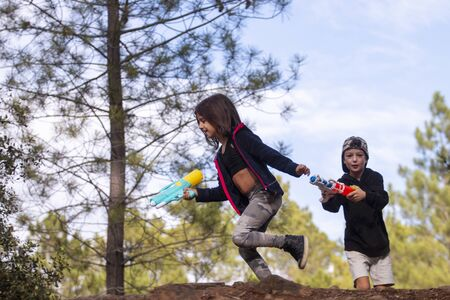 Cute girl and boy with water guns playing a game on outdoor forest.