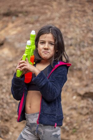 Cute girl with water gun playing a game on outdoor forest.