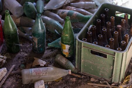View of a bunch of abandoned beer and soda bottles on a barn. Stock Photo
