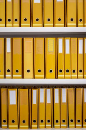 Aligned yellow binders on a office space.