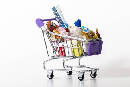 Miniature shopping cart full with goods isolated on white background.