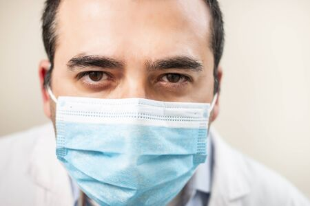 caucasian doctor with face mask portrait on a white background.