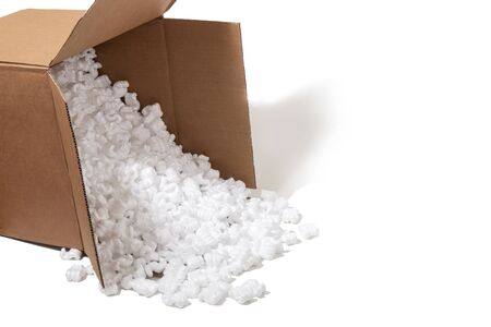 Cardbox spills plenty of polystyrene  packing pieces used for minimize bumps in transportation of goods. Stock Photo