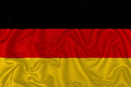 Germany country flag on wavy silk textile fabric background.