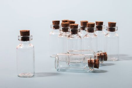 Glass bottles with cork isolated on a light blue background.