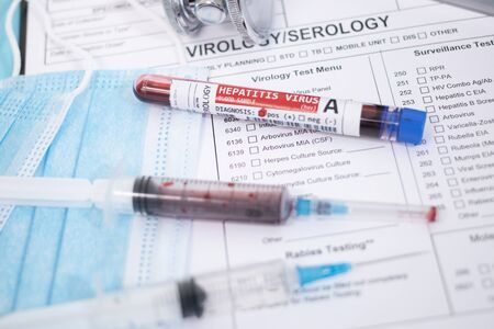Fictional Blood samples with infected hepatitis A virus, with mask, syringe and lab report.