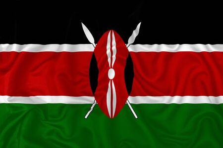 Kenya country flag on wavy silk textile fabric background.