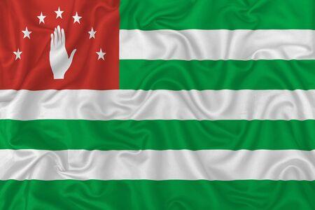 Abkhazia state flag on wavy silk textile fabric background.