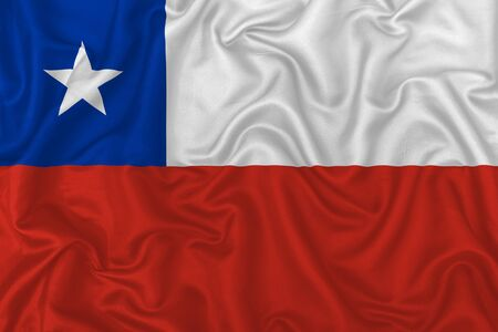 Chile country flag on wavy silk textile fabric background. 版權商用圖片