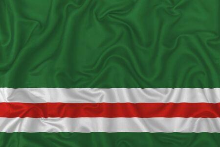 Chechen Republic of Ichkeria (1991-2000) flag on wavy silk textile fabric background. 版權商用圖片