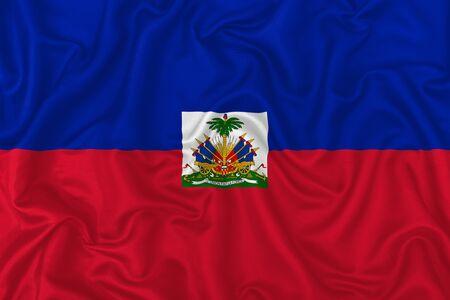 Haiti country flag on wavy silk textile fabric background.