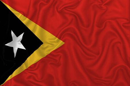 East Timor country flag on wavy silk textile fabric background.