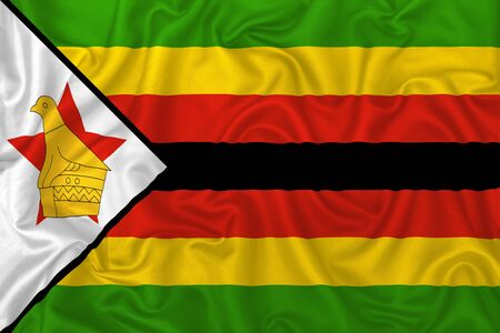 Zimbabwe country flag on wavy silk textile fabric background.