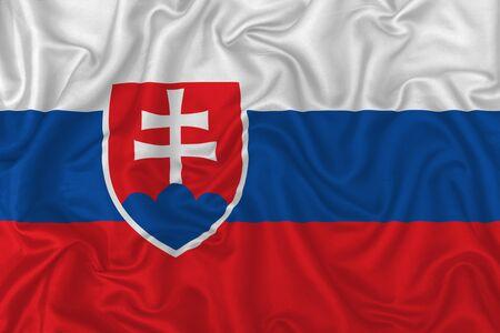 Slovakia country flag on wavy silk textile fabric background. 版權商用圖片