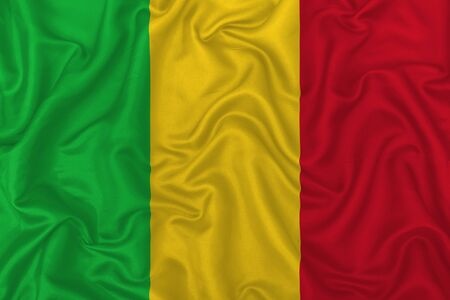 Mali country flag on wavy silk textile fabric background.