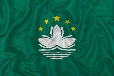 Macau city flag on wavy silk textile fabric background. 版權商用圖片