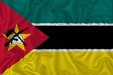 Mozambique country flag on wavy silk textile fabric background.