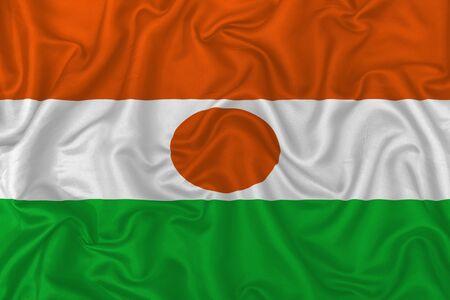 Niger country flag on wavy silk textile fabric background. 版權商用圖片