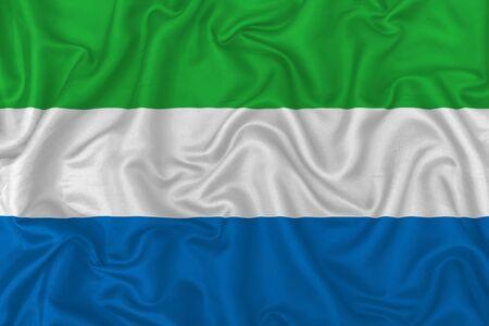 Sierra Leone country flag on wavy silk textile fabric background. 版權商用圖片